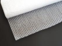 Rolo transparente do invólucro com bolhas de ar para empacotar artigos frágeis na opinião superior do fundo preto imagem de stock