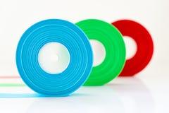 Rolo verde vermelho isolado, foco seleto da fita azul no azul Imagens de Stock