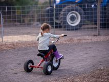 A girl riding a tricycle bike with a large tires royalty free stock images