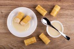Rolos da bolacha com leite condensado nos pires, colher na bacia com leite condensado, rolos na tabela Vista superior imagens de stock