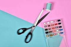 Rolos da linha e tesouras, grupo de linha colorida na mesa da costura Foto de Stock