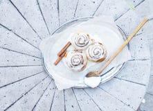 Rolos de canela com as varas da crosta de gelo e de canela do queijo creme Foto de Stock