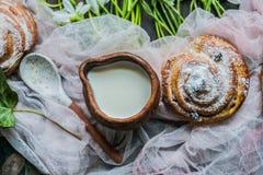 Rolos de canela com leite e flores em um dia ensolarado foto de stock
