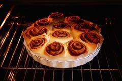Rolos de canela no formulário para a repreensão no forno em processo do cozimento imagem de stock