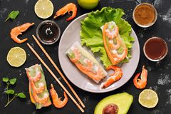 Rolos de mola vietnamianos com camarões, abacate, alface, molhos, hashis Fundo concreto preto, close up da vista superior imagens de stock royalty free