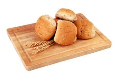 Rolos de pão em uma placa de madeira imagens de stock royalty free