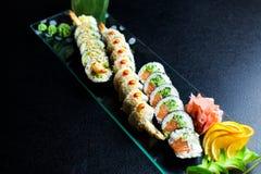 Rolos de sushi ajustados servidos na placa de vidro Imagens de Stock