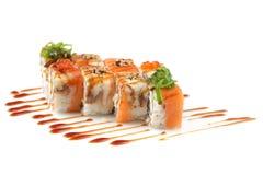 Rolos de sushi com banana e salmões no branco Imagens de Stock
