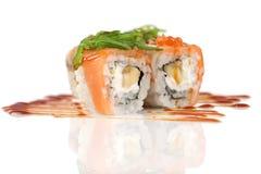 Rolos de sushi com banana e salmões no branco Fotografia de Stock