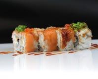Rolos de sushi com banana e salmões no branco Foto de Stock Royalty Free