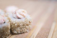 Rolos de sushi com close-up do sésamo e do molho no defocus Fotografia de Stock Royalty Free