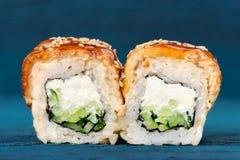 Rolos de sushi com o queijo creme, o nori e o pepino cobertos com a EE Foto de Stock Royalty Free