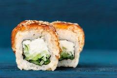 Rolos de sushi com o queijo creme, o nori e o pepino cobertos com a EE Fotos de Stock