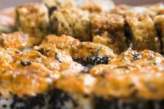 Rolos de sushi com salmões, o caviar preto e o tiro do macro do close-up do sésamo Foto de Stock