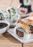 Rolos de sushi com varas e molho de soja Foto de Stock