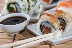 Rolos de sushi com varas e molho de soja Fotos de Stock