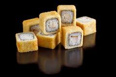 Rolos de sushi cozidos com bacon em um close-up preto do fundo Fotos de Stock