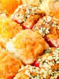 Rolos de sushi cozidos com o close up alaranjado e vermelho das ovas Fotos de Stock