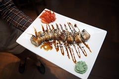 Rolos de sushi dourados do dragão com atum, enguia, pepino, sementes de sésamo em uma placa branca com wasabi e imbrem foto de stock