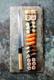 Rolos de sushi e nigiri com faca japonesa imagem de stock royalty free