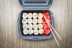 Rolos de sushi em um recipiente em uma tabela de madeira Vista superior imagens de stock royalty free