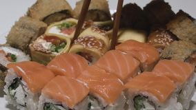 Rolos de sushi em um rolo de sushi da placa com as varas da tomada da panqueca do ovo video estoque