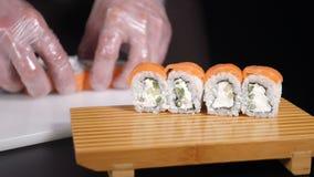 Rolos de sushi frescos e saborosos V?deo do alimento Servido na placa de madeira Mãos que põem o sushi Os rolos de sushi mestres  filme