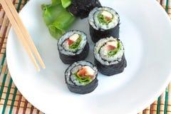Rolos de sushi no close up branco da placa Fotos de Stock