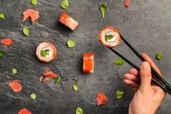 Rolos de sushi que mantêm a mão humana com hashis Fotos de Stock Royalty Free