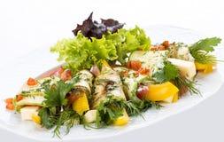 Rolos do abobrinha com queijo e vegetais em uma placa branca fotos de stock royalty free