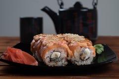 Rolos do rolo, da Califórnia de sushi de Philadelphfia com gengibre e wasabi na placa preta imagens de stock royalty free