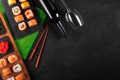 Rolos do sashimi e de sushi do grupo do sushi, garrafa do vinho e um vidro servido na ardósia de pedra fotografia de stock royalty free