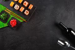 Rolos do sashimi e de sushi do grupo do sushi, garrafa do vinho e um vidro servido na ardósia de pedra fotografia de stock