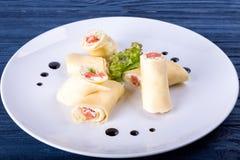 Rolos Salmon do lavash com queijo e ervas na placa de vidro, fim acima da vista fotografia de stock royalty free