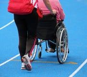 rolstoel met een bediende op het atletische spoor tijdens SP royalty-vrije stock fotografie