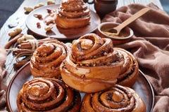 Rolt de vers gebakken Kaneel broodje, omhoog sluit stock afbeeldingen