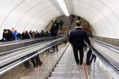 Roltraproltrap binnen de Ondergrondse Metro Post Mensen die de stappen van de roltrap beklimmen Ondergrondse metro stock fotografie