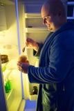 微笑的roly多人在晚上采取瓶子用从冰箱的果酱 库存照片