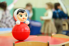 Roly-poly toy stand at table in kindergarten. Bright red roly-poly toy stand at table in kindergarten; children play Stock Photography