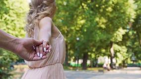Romántico sígame tiro del blonde hermoso que lleva a cabo las manos con el hombre querido metrajes