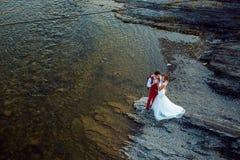 Romántico sobre el retrato de los recienes casados sonrientes que abrazan blando en la orilla del río durante el día soleado fotos de archivo