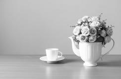 Romántico un ramo de rosas en el jarro blanco con la taza de café en la tabla de madera y los muros de cemento grises, color gris foto de archivo libre de regalías