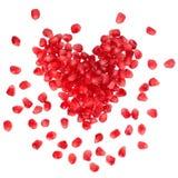 Romã dispersada da grão na forma de um coração Foto de Stock