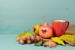 Romã, folhas de outono e copo de chá sobre o fundo de madeira Imagens de Stock