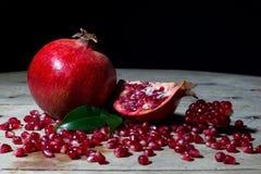 Romã vermelha com fatias e sementes no pranchas de madeira velhas no preto Imagem de Stock Royalty Free