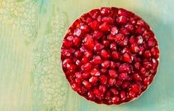 Romã vermelha saboroso das grões na bacia pequena em uma tabela rústica verde fotografia de stock royalty free