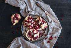 Romã descascada madura vermelha na placa de metal rústica e na toalha de cozinha bege sobre o fundo escuro Imagens de Stock Royalty Free