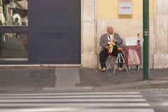 Rom, Italien, am 9. Oktober 2011: Älterer Mann spielt Saxophon am Eingang zur Bank lizenzfreie stockfotos
