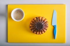 ROM-Kuchen auf dem gelben Hintergrund mit Schale Latte Stockfoto