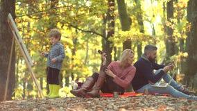 Rom?ntico y amor Follaje de ca?da Familia alegre que tiene comida campestre Madre y padre con el hijo que se divierte al aire lib almacen de metraje de vídeo